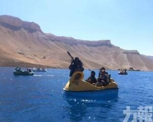 塔利班士兵持槍坐腳踏船遊玩